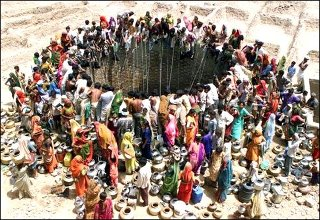 Women of Gujarat State, India, throng a well.