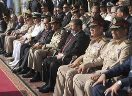 President Morsi (Center) in a crowd of military brass at his swearing in ceremony.