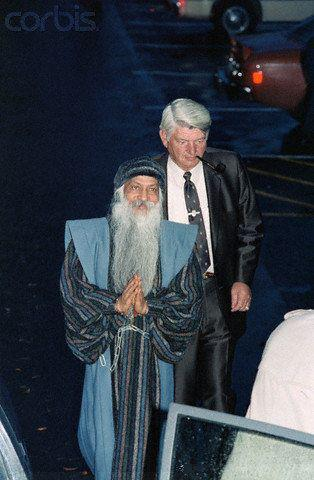 Osho arrested and in chains. He was later poisoned by talium while incarcerated without a warrant by the Reagan Administration. He was eventually released but the poison aged him 20 years in four and he died in January 1990.