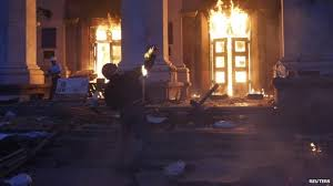 Ukrainian ultra-nationalist throwing Molotov cocktail into Odessa's Trade Union building where dozens were trapped by mobs and burnt to death.