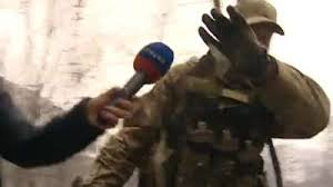 Ukrainian soldier with American accent hiding face to reporter in Mariupol.