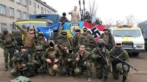 "Here is the Azov Battalion taking a break from fighting the Ukrainian Civil War to show their blue and yellow Ukrainian banner with the reversed SS Nazi symbol (center) and a Swastika. To them, Bandera is the ""George Washington"" of Ukraine."