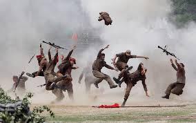 South Korean soldiers hamming it up in mock battle, costumed in North Korean uniforms.