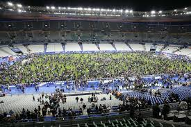 "Crowds of soccer fans gather on the field of the Stade de Paris waiting for security to give them the ""all clear."""