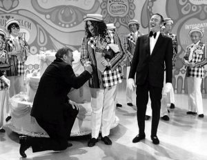 "Tiny Tim successfully hand-shake crushes John Wayne on Laugh-in. All in good fun as we ""tip toe through the tulips"" in falsetto voice like he used to sing it with his Cooky Ukulele."