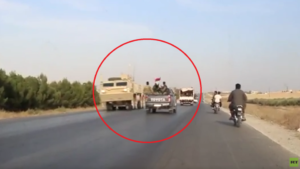 A US armored personnel carrier (left) in a convoy of US forces leaving Manbij, Syria, while a convoy of Syrian Arab Army forces (center) passes it, racing on its way to take up positions alongside the Kurds against a Turkish Army Invasion. Source: Ruptly.
