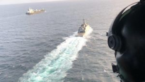 Venezuelan Navy helicopter and frigate escorting the first of a fleet of Iranian tankers into port.