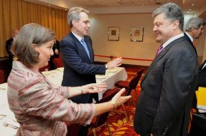 June 2014, then assistant Secretary of State Victoria Nuland (left), the architect of the US-created Ukrainian government after the 23 February 2014 neo-Nazi coup in the Maidan Revolution. Alongside is her puppet-government arranging accomplice US Ambassador Pyatt (center). They are seen here greeting the new president-elect of Ukraine Poroshenko (right) before a meeting held in Warsaw. Former Obama Secretary of State (current Climate Change Czar under Biden) can be seen extreme right. Source: US Government.